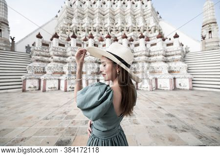 Young Asian Woman Is Enjoy Sightseeing And Traveling At Wat Arun Temple In Bangkok, Thailand.