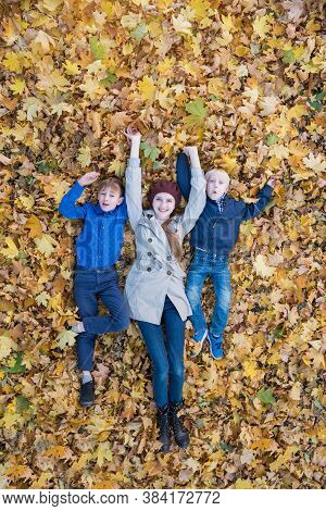 Cheerful Family Fooling Around In Park. Mother And Two Children Lying Down In Big Pile Of Leaves. To