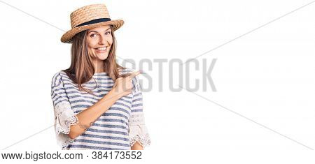 Beautiful caucasian woman wearing summer hat cheerful with a smile of face pointing with hand and finger up to the side with happy and natural expression on face