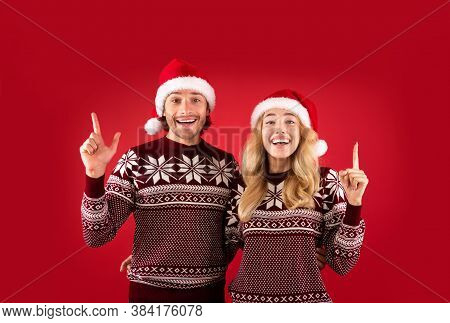 Joyful Millennial Couple In Woolen Sweaters And Santa Hats Pointing Upwards Over Red Background