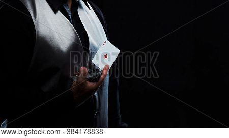 Magician illusionist showing performing card trick. Close up of hand and poker cards on black background.