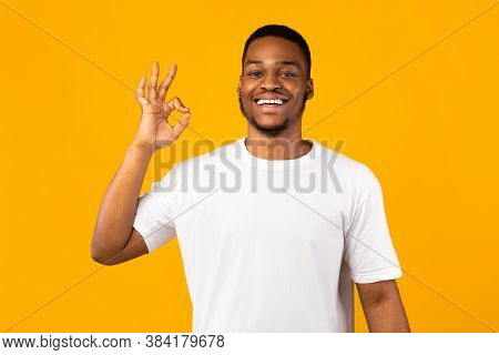 Okay Concept. Positive African Man Gesturing Ok Sign Smiling To Camera Posing On Yellow Studio Backg