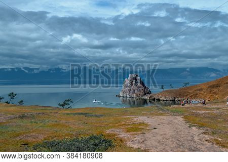 Cape Shamanka Rock In Blue Lake Baikal Among The Grassy Steppes, Against The Background Of Mountains