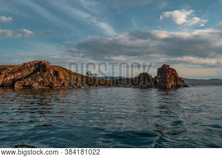 Red Cape Shamanka In Clear Blue Lake Baikal Among The Rocks, Mountains And Clouds, Sunset, Ripples