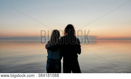 Silhouetted Couple Embracing While Watching Beautiful Sunset On The River Together, Back View, Web B