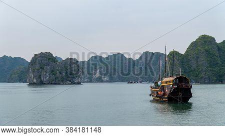 Cat Ba, Vietnam - November 19, 2019 : Junk Boat Cruising In Lan Ha Bay Near Ha Long Bay, Mountain Ka