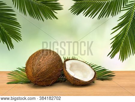 Coconut (cocos Nucifera) With Half And Palm Leaves On Wooden Table On A Background Tropical Leaves P