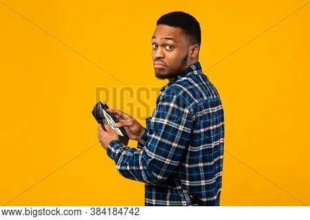 Low Salary. Discontented Black Man Holding Wallet With Cash Money Looking At Camera Standing On Yell