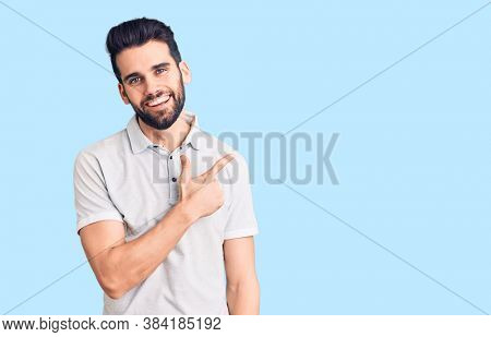Young handsome man with beard wearing casual polo cheerful with a smile of face pointing with hand and finger up to the side with happy and natural expression on face