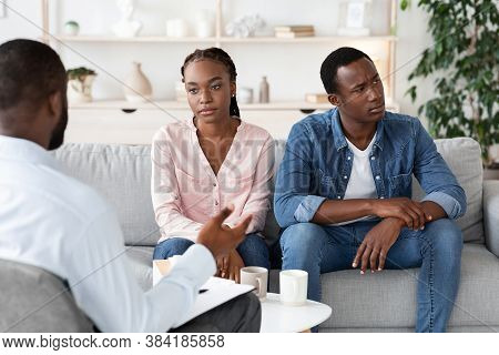 Couples Therapy. Depressed African Spouses Sitting On Couch At Counselors Office, Suffering From Rel