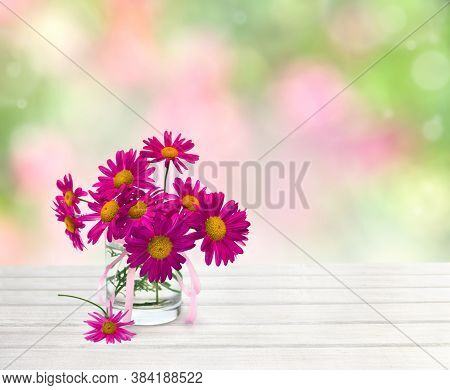 Bouquet Of Flowers Pink Daisies ( Pyrethrum, Tanacetum Coccineum ) In Small Vase On White Wooden Tab