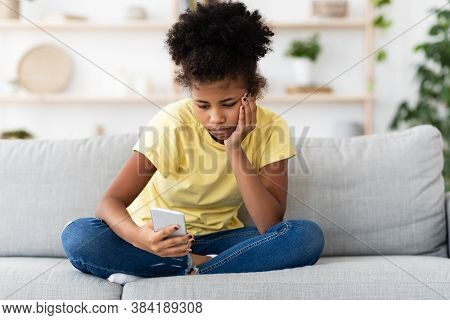 Bored African American Teen Girl Using Smartphone Browsing Internet Sitting On Sofa At Home. Modern