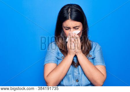 Young beautiful woman sick for flu. Using paper handkerchief on full nose of mucus standing over isolated blue background