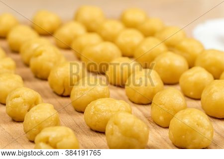 Small Balls Of Fresh Homemade Cookie Dough On A Wooden Board, Macro, Background