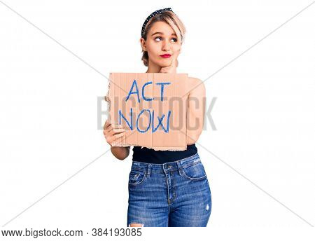 Young beautiful blonde woman holding act now banner serious face thinking about question with hand on chin, thoughtful about confusing idea