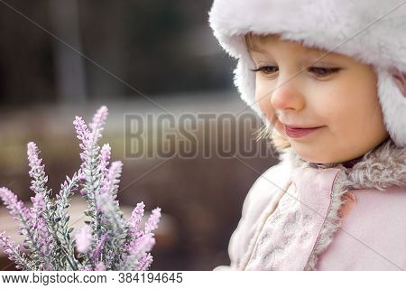 Little Girl In A Flower In Her Hand Against The Background Of The City, Spring, Pink Clothes
