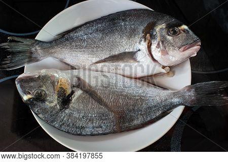Market Frozen Silver Sea Bream Raw Uncooked Fish Sat On A White Plate
