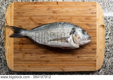 Market Frozen Silver Sea Bream Raw Uncooked Fish Top View Sitting On A Wooden Board On A Kitchen Cou
