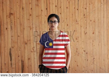 Woman Wearing Malaysia Flag Color Shirt And Standing With Two Hands In Pant Pockets On The Wooden Wa