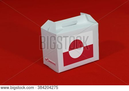 Greenland Flag On White Box With Barcode And The Color Of Nation Flag On Red Background. The Concept