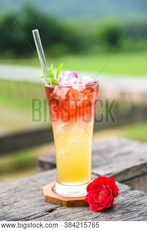 Tea Flowers Made From Tea Rose Petals In A Glass On Wooden Table And Nature Green Background / Iced