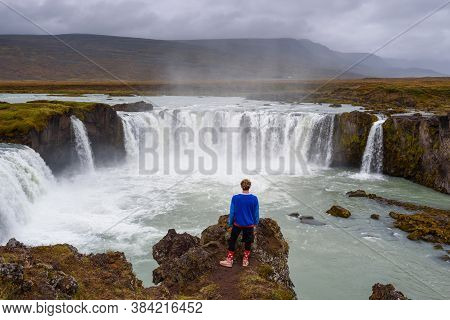 Young Hiker Standing At The Godafoss Waterfall In Iceland. Godafoss Means The Waterfall Of The Gods