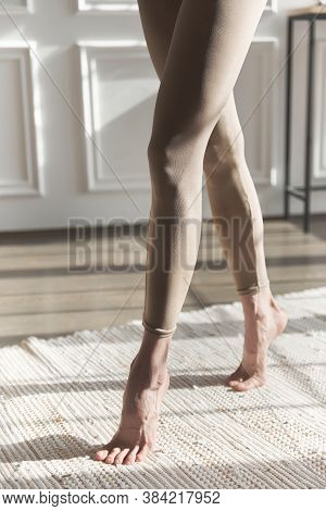Fit Long Woman Legs In Leggings. Close Up Slim, Slender, Shapely Legs In Beige Skin-tight Sweatpants