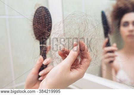 A Woman Pulls A Bunch Of Hair From Her Comb. Rear View. In The Background, A Reflection In The Mirro