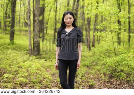 A Chinese Woman Standing In A Springtime Forest In Bushkills Falls, Pennsylvania During The Day.