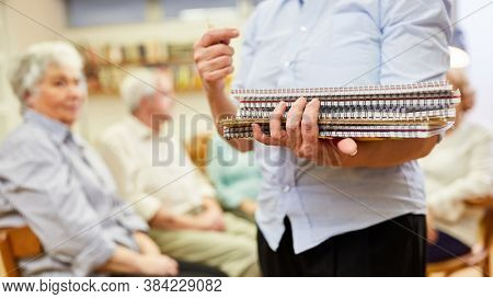 Therapist with writing pads for writing therapy or painting therapy in a retirement home