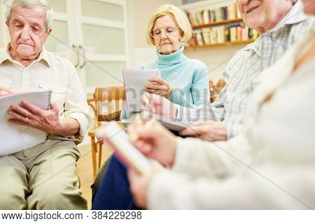 Senior group with writing pad or drawing pad in a writing therapy