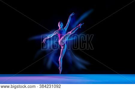 Flying Bird. Young And Graceful Ballet Dancer On Black Studio Background In Neon Mixed Light. Art, M