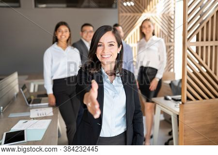 Caucasian Businesswoman Extending Her Hand For A Handshake With Colleagues Standing In Background