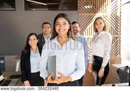 Confident Hispanic Businesswoman Standing In Office With Colleagues In Background
