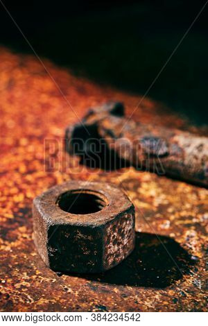 closeup of a rusty nut and a rusty bolt, on a rusty surface