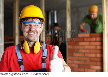 Portrait Of Foreman Or Supervisor Of Group Of Builders. Man Showing Ok Gesture, Guarantee For Qualit