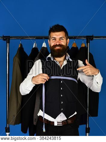 Man With Beard By Clothes Rack. Shop Assistant Or Seller