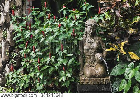 Female Stone Carved Statuette As Fountain In Balinese Traditional Garden. Traditional Element Of Arc