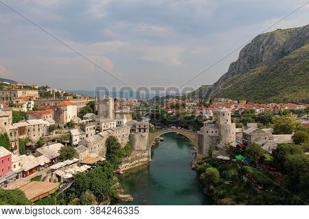 A Landscape View Of The Old Town Of Mostar, With The Old Arched Bridge Over The Neretva River, With