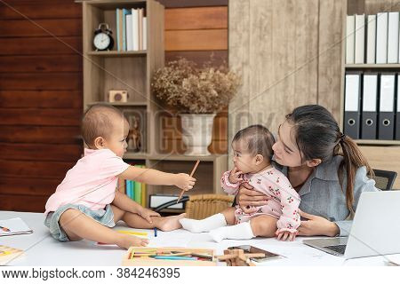 Busy Woman Trying To Work While Babysitting Two Kids.  Young Asian Mother Talking And Playing With T
