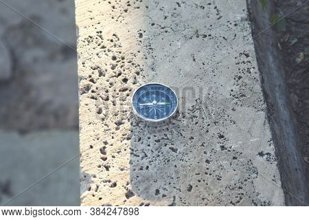 Compass On A Stone At The Top Of A Mountain.