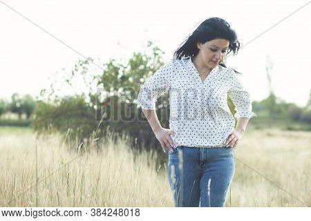 Beautiful Sexy Brunette Girl In Shirt And Jeans Posing On The Field.