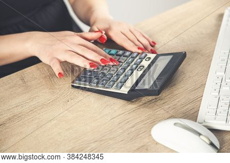 Female Hands With Red Nails On A Calculator Keyboard.