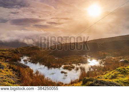 Fog, Mist And Dramatic Sky Over A Swamp Or Bog With Sun Reflecting In A Puddle. Dramatic Landscape O