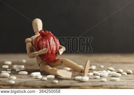 Toy Man Holds An Anatomical Heart In His Hands, Sits Next To Pills. Cardiovascular System Treatment,
