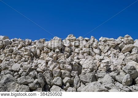 big pile of rocks and boulders piled in a heap under a blue clear sky