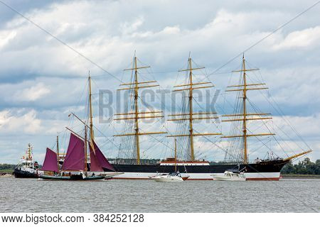 Hollern-Twielenfleth, Germany - September 7, 2020: Historic barque PEKING moored on Elbe river waiting to be towed to German Port Museum at Hamburg, accompanied by other historic and modern vessels.