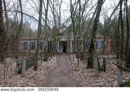 The Facade Of An Abandoned Kindergarten In The Chernobyl Radioactive Zone. Autumn Foliage On The Gro