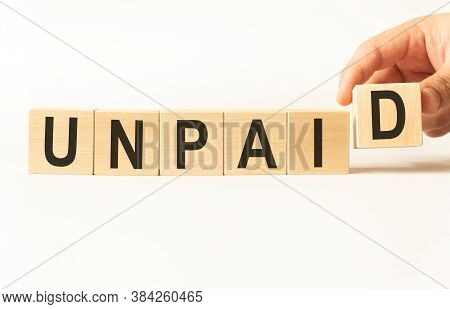 Word Unpaid. Wooden Small Cubes With Letters Isolated On White Background With Copy Space Available.