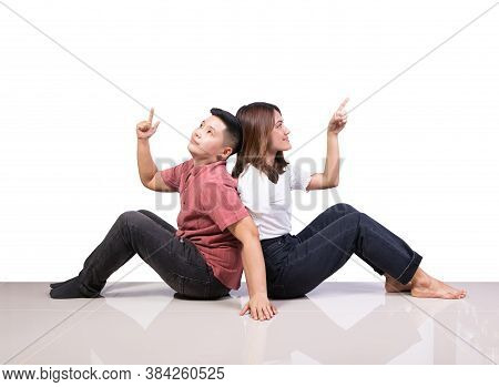 Two Smiling Woman Young Girls And Happiness Tomboy Sitting On Tile Floor Finger Point Above With Whi